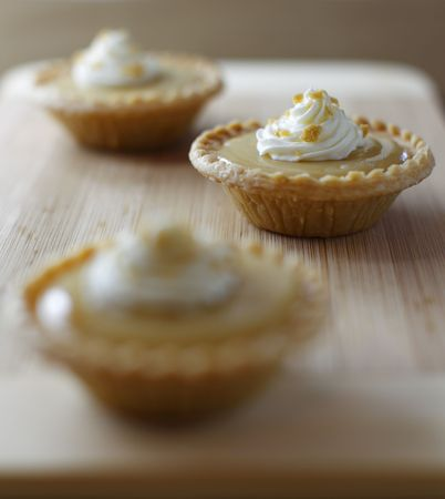 mini maple syrup tart on a wooden board with a fork. Focus on the middle portion.Shallow depth of field. photo