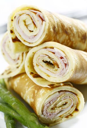 rolled ham and cheese crepe with asparagus on a white background. Stock Photo
