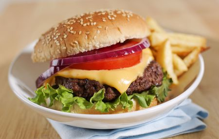 cheeseburger with french fries on a white plate. Shallow depth of field. Stockfoto