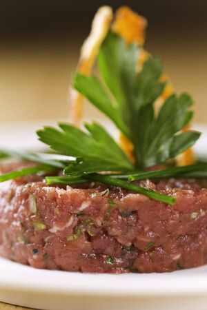 Loin beef tartar on a white plate with parsley on the top. Very shallow depth of field.Focus on the front of the meat. Stock Photo - 7946840