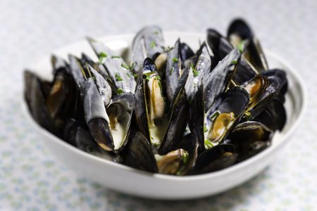 Mussel with white wine sauce  on a plate. Very shallow depth of field. photo