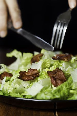 Somebody eating a fresh caesar salad in a plate with big piece of bacon on it. Very shallow depth of field. photo