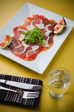 Red beef carpaccio in a white plate with salad, fig fruit, parmesan cheese and olive oil. Yellow background and shallow depth of field. Stock Photo - 8603105