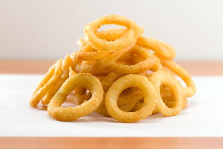 waxed: Stacked onion ring on a white waxed paper. Very shallow depth of field.