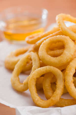 waxed: Stacked onion ring on a white waxed paper. Honey sauce  in the backgroundVery shallow depth of field.  Foto de archivo