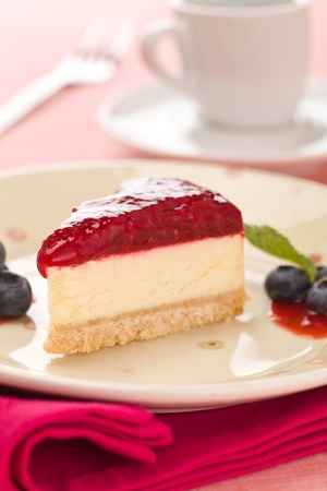 Piece of raspberry cheese cake in a plate with  fork and coffee cup in the background. Extremely shallow depth of field.