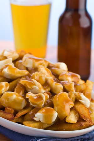 Poutine meal made with french fries, cheese curds and gravy. Beer in the background. Shallow depth of field. Stock Photo