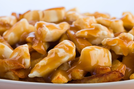 jus: Poutine meal made with french fries, cheese curds and gravy. Macro photography with shallow depth of field.