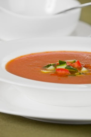 gaspacho: Cold soup called gaspacho in white dishware. Focus is on tomato and cucumber piece. Very shallow depth of field. Stock Photo