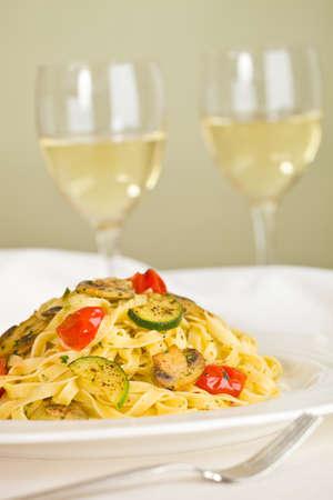 Vegetarian tagliatelle pasta with mushroom,zukini,cucumber, tomato and pesto sauce. White wine and green background. Very shallow depth of field. photo