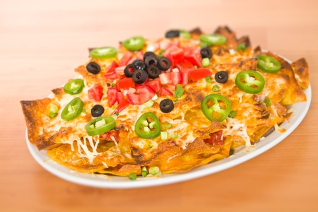 Fresh cheese nacho with vegetable on the top. Very shallow depth of field. photo