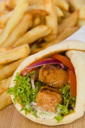 Gyros pita sandwich with chicken souvlaki meat and vegetable. French fries in the background. Very shallow depth of field. Stock Photo