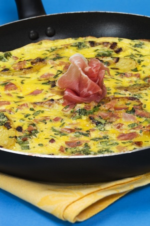 cookware: Frittata with potato, basil leaf, prosciutto meat and egg in a cookware pan. Shallow depth of field.