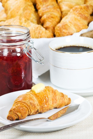 croissant with melted butter on it. Strawberry jam and black coffee in the background. Shallow depth of field. photo