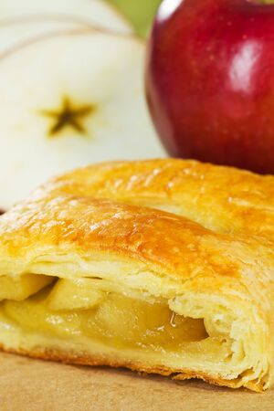 turnover: Apple turnover with fruit in the background. Very shallow depth of field.  Stock Photo