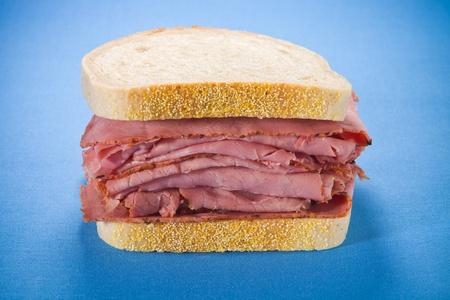 青色の背景に肉ビーフ サンドイッチをスモークしました。