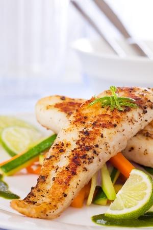 pesce cotto: Arrosto di pangasio farine di pesce con verdure in un piatto bianco.