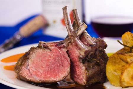 rack of lamb: lamb chop meal with potato and carrot. Red wine with a glass in the background. Very shallow depth of field.  Stock Photo