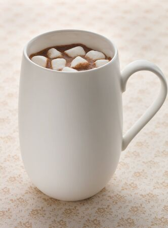 Hot chocolate drink on a brown background with marshmallow.