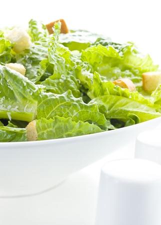 Caesar salade op wit met parmezaanse kaas.