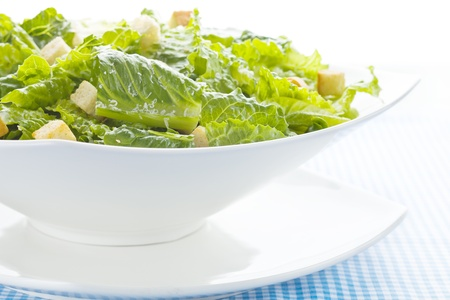 Caesar salad on white with parmesan cheese.