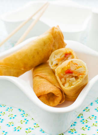 Close up spring roll in a white bowl.  photo