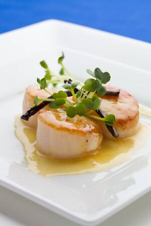 Close up Scallop seafood appetizer with vanilla stick and sauce.  Stock Photo