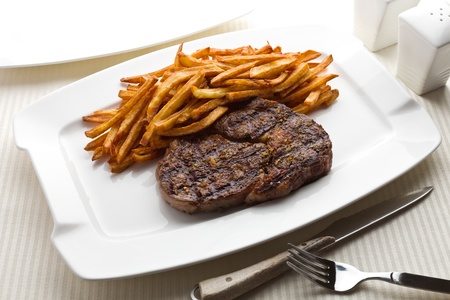 Steak and french fries on a white plate.