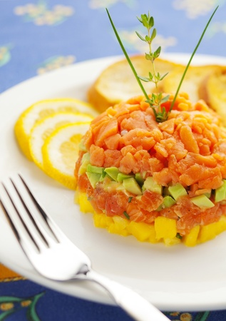 tartar: fresh salmon tartar with avocado and pineapple in a white plate.