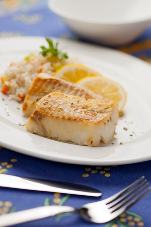 Fresh cooked cod fish with rice and lemon photo