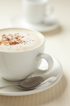 Cappuccino coffee with cocoa powder on the top. Brown tint.  Stock Photo