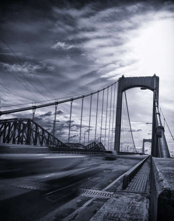 vignetting: Bridge from canada with fast moving car on the road. Black and white with blue tint and vignetting added. Editorial