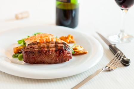 Surf and turf meal with fresh scampi and steak. Red wine in the background and shallow depth of field. Stock Photo