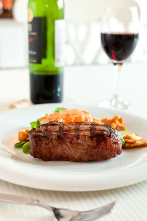 white wine: Surf and turf meal with fresh scampi and steak. Red wine in the background and shallow depth of field. Stock Photo