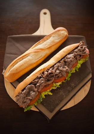 Beef meat sandwich with baguette bread on the side. Very shallow depth of field. photo