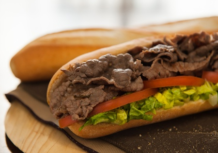 Beef sandwich with tomato and salad on a table. Very shallow depth of field. Stock Photo