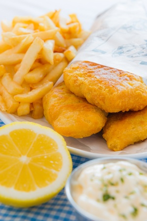 English fish and chips meal with mayonaise sauce and french fries on the side. Shallow depth of field. Stock Photo - 12873952