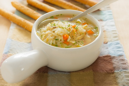 meat soup: Healthy chicken rice soup with spoon. Shallow depth of field. Stock Photo