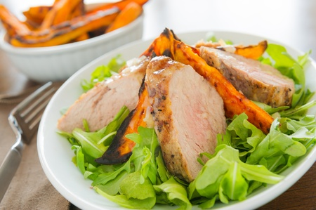 Healthy meal with sliced pork fillet with sweet potato and salad. Shallow depth of field. Stock Photo - 12874000