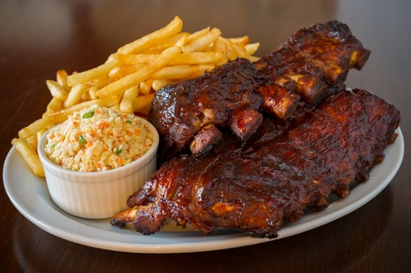 costela: Pork ribs back with french fries and coleslaw salad on the side. Shallow depth of field.