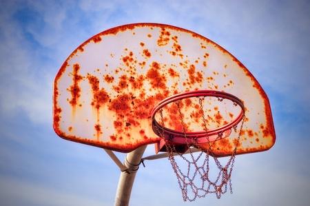 panier basketball: Panier de basket vieux et rouill� avec un ciel bleu nuageux en arri�re-plan.