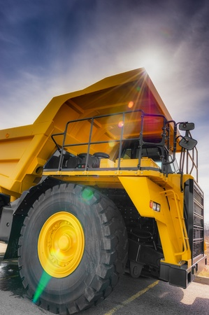 dumps: Large haul truck with controled flare and dark blue sky. Stock Photo