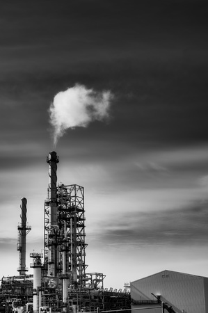 oil and gas industry: Oil refinery with smoke from the chemney.Black and white with high contrast.
