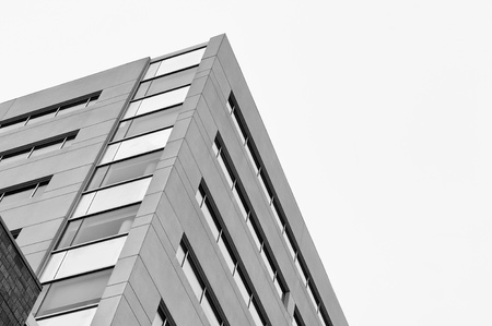 administrative buildings: High rise top corner with white sky in the background. Black and white photography.
