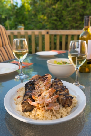 Outdoor meal with chicken and shrimp brochette on the rice. Alcohol white wine. Very shallow depth of field. photo