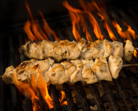 Chicken brochette cooking on a barbecue grill with flame and fire. Shallow depth of field.