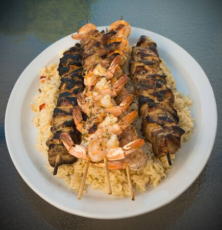 Chicken and shrimp brochette on rice. Very shallow depth of field. photo