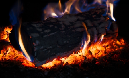 Beautiful wood log burning in a stove with flame around  Low key image  Shallow depth of field  photo
