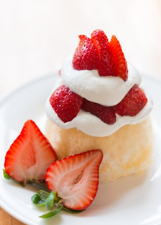 Strawberry shortcake on a white plate. Very shallow depth of field.
