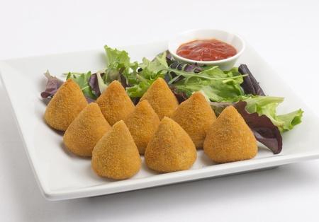 Coxinha de Galinha - Braziliaanse gefrituurde kip snack, populair bij lokale partijen. Geserveerd met salade en chilisaus.
